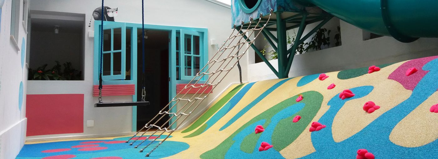 Outdoor playground built into a small courtyard with a rope climbing frame.