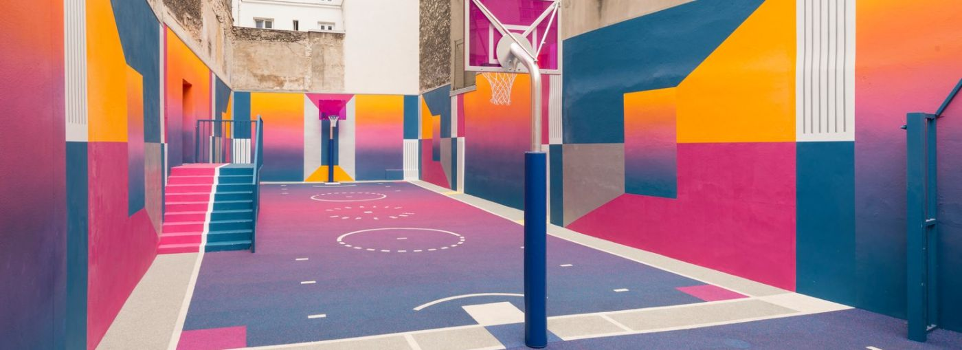 Outdoor basketball court with coloured floor made with a gradient from pink to blue.