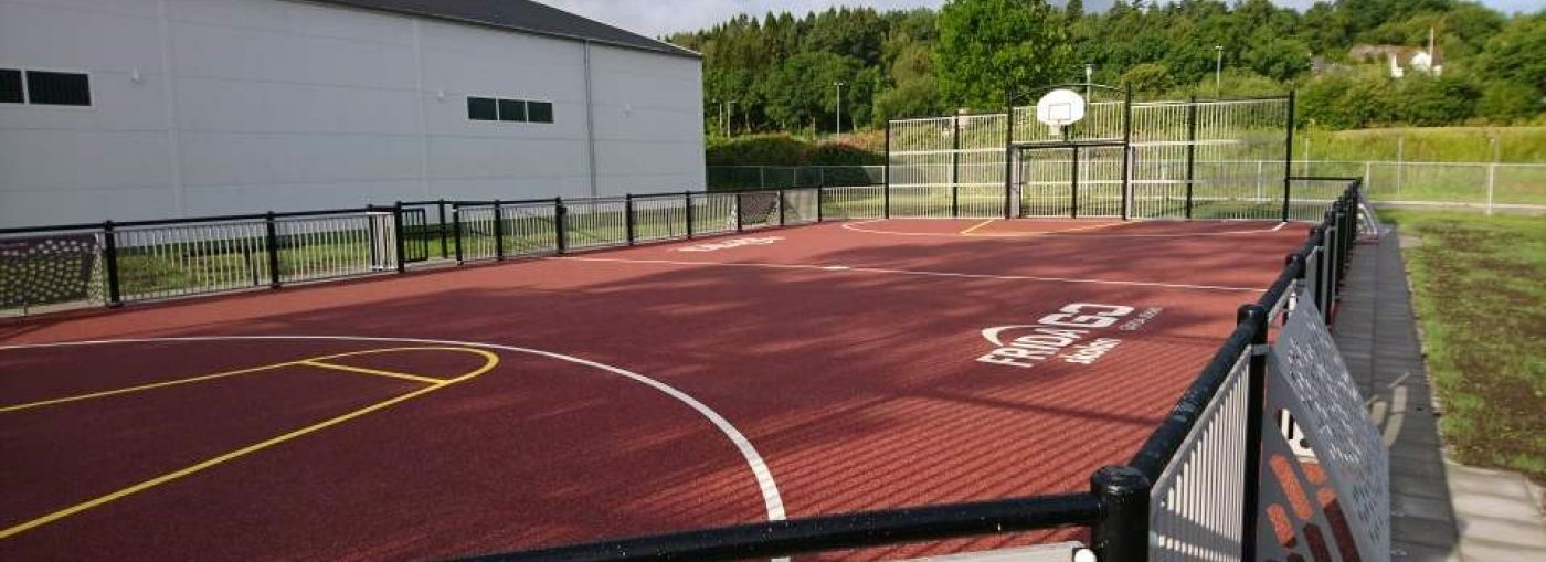Outdoor basket court with a red floor in a school.