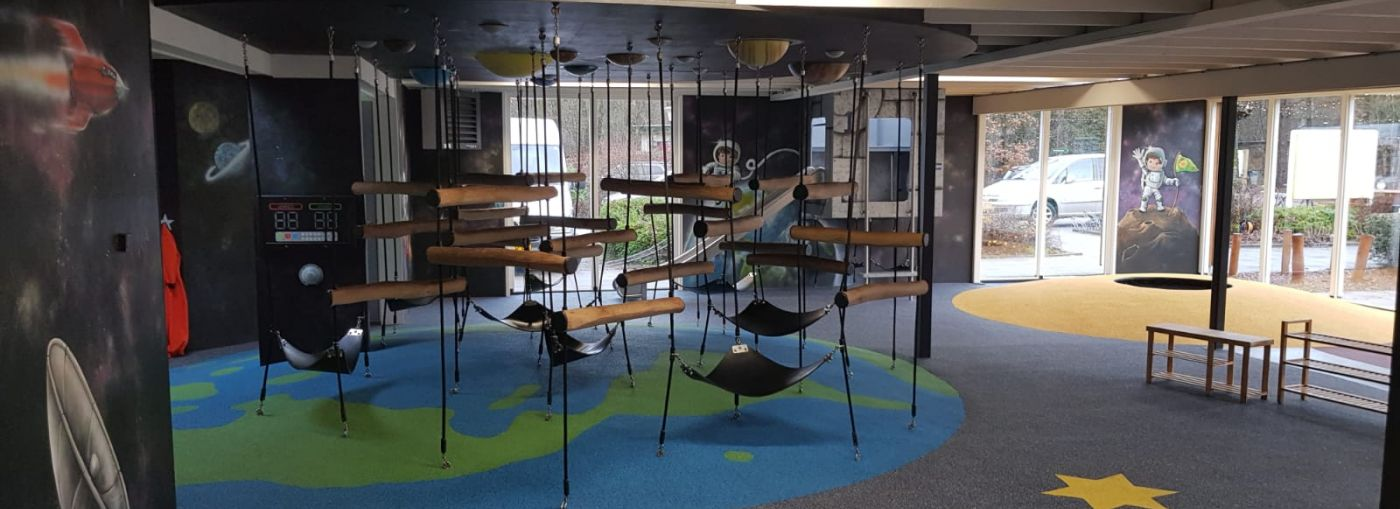 Indoor playground with rubber flooring and a climbing frame.