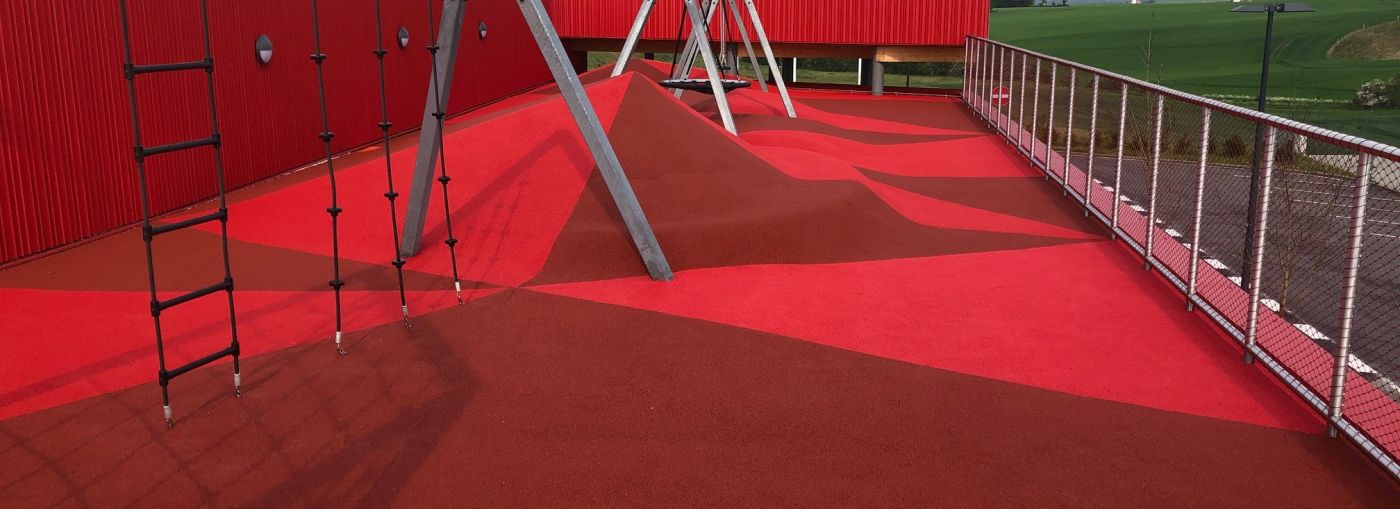 Outdoor playground with climbing frames with the entire floor made with red coloured rubber granules.