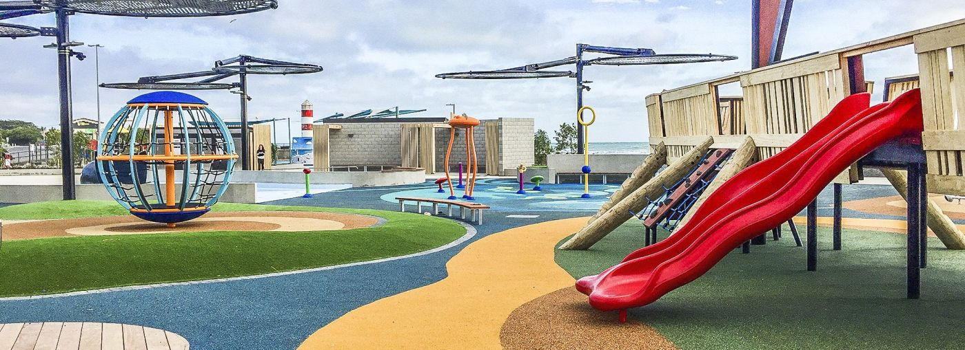 Outdoor playground with multi-coloured rubber flooring.