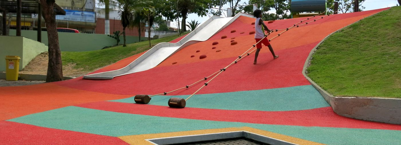 A kid climbing up a hill that has been covered in a colourful rubber flooring.