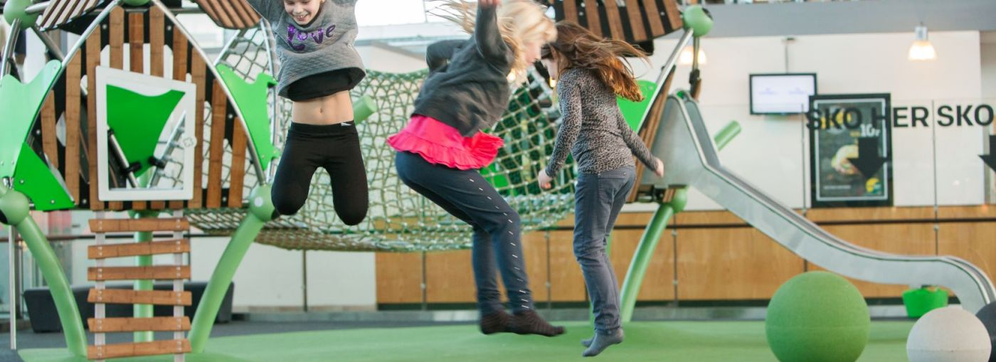 Three girls jumping on an indoor rubber floor playground.