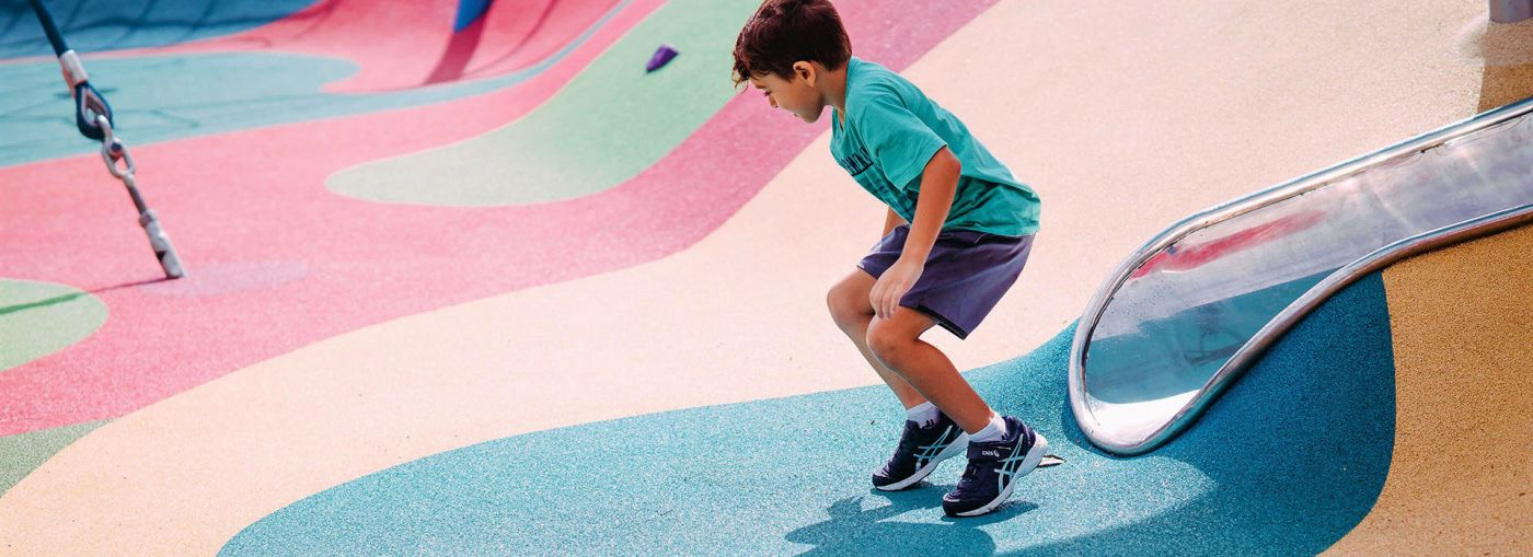 A young boy standing up after going down a slide that has been built into colourful rubber playground flooring.